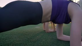 Two young womans doing plank exercise on field in park during sunset, fitness models exercising.  stock footage