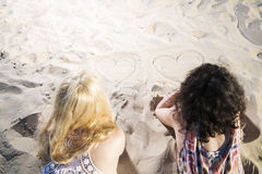 Two young womans draw hearts on sand. Royalty Free Stock Images