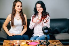 Two young womans reviewing beauty products on video blog at home. Two Beautiful young womans reviewing beauty products on video blog at home Royalty Free Stock Images
