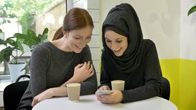 Two young womans sitting in cafe, one of them muslim woman in hijab, looking at phone and laughing, looking in camera.  stock video footage