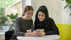 Two young womans sitting in cafe, one of them muslim woman in hijab, watching phone and looking in camera, smiling.  stock video