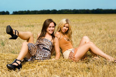 Two young women. Sitting in the field Royalty Free Stock Images