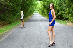 Two young women. Two women walking on the road. Focus on brunette stock image