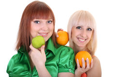 Two young women with apple and oranges Stock Image