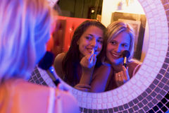 Two young women applying makeup in a nightclub stock images