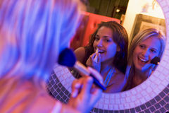Two young women applying makeup in a nightclub Royalty Free Stock Photography