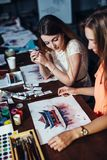Two young women attending aquarelle painting classes for adults at art school. A girl showing her artwork to friend. Two young women attending aquarelle Royalty Free Stock Image
