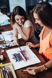 Two young women attending aquarelle painting classes for adults at art school. A girl showing her artwork to friend. Two young women attending aquarelle stock photos