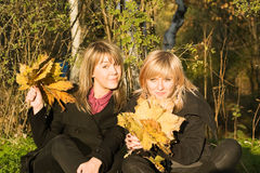 Two young women with autumn leaves Royalty Free Stock Images
