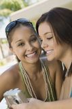 Two young women in back yard looking at photos on digital camera Royalty Free Stock Image