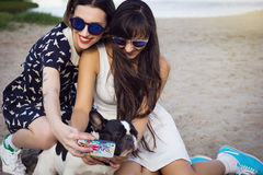Two young women on beach taking photo with french bulldog. Two beautiful young women on the beach taking selfie photo with french bulldog royalty free stock image