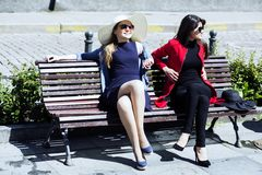 Two young women on a bench sunbathing Stock Photos
