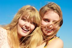 Two women best friends having fun outdoor. Two young women best friends blonde cheerful girls having fun outdoor against blue sky wind blowing in hair. Summer Stock Images