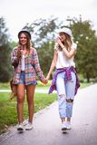 Two young women holding hands walking in green park. Best friends. Two young women best friends walking on summer day in green park stock images