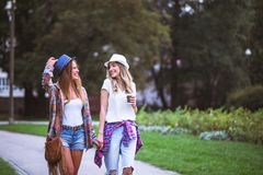 Two young women holding hands walking in green park. Best friends. Two young women best friends walking on summer day in green park stock photography