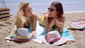 Two young women in bikinis enjoying the beach. As they lie sunbathing on their towels close to the edge of the sea stock video footage