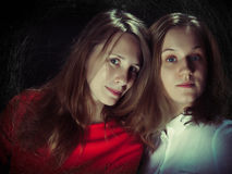 Two young women on a black background Royalty Free Stock Image