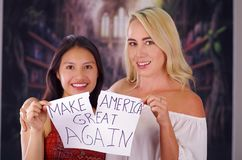 Two young women blonde and latin girl smiling and breaking racism idiosyncrasy from a american person and foreign people. Destroying a paper that is written Stock Image