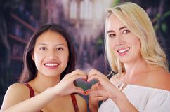 Two young women blonde and latin girl smiling and breaking racism idiosyncrasy from a american person and foreign people. Both doing a heart sign with teir Stock Photography