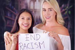 Two young women blonde and latin girl smiling and breaking racism idiosyncrasy from a american person and foreign people. Holding a piece of paper that is Stock Image