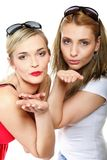 Two young women blowing kisses to the camera Royalty Free Stock Images