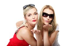 Two young women blowing kisses to the camera Royalty Free Stock Image