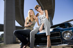 Two young women on bonnet of car beneath overpass, smiling, low angle view Royalty Free Stock Photo