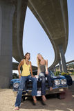 Two young women on bonnet of car beneath underpass, low angle view Royalty Free Stock Image