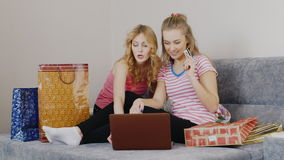 Two young women bought items online. Sit on the bed in the bedroom, about their shopping bags and laptop stock video
