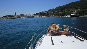Two young women on the bow of the boat enjoying. The scenery, montenegro stock video footage