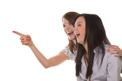 Two young women breaking into laughter. Two young girls to see something very funny and laugh Stock Images
