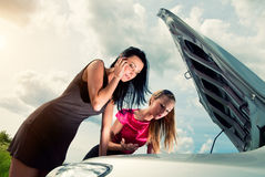 Two young women with broken car Royalty Free Stock Photos