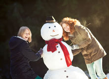 Two young women building a snowman Royalty Free Stock Photo