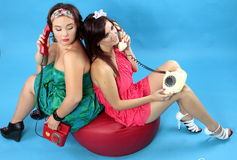 Two young women calling on phones on blue background. Two young women: left size girl in green dress and red phone in hand and at right size girl in red dress Stock Images