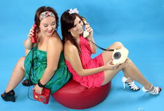 Two young women calling on phones on blue background. Two young women: left size girl in green dress and red phone in hand and at right size girl in red dress Stock Image