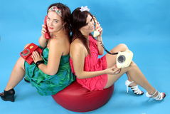 Two young women calling on phones on blue background. Two young women: left size girl in green dress and red phone in hand and at right size girl in red dress Stock Photography