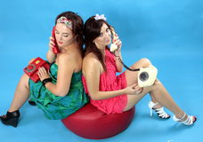 Two young women calling on phones on blue background. Two young women: left size girl in green dress and red phone in hand and at right size girl in red dress Stock Photo