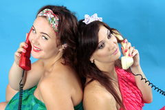 Two young women calling on phones on blue background. Two young model women calling on phones on blue background, women in green dress keep smile and take in Royalty Free Stock Image