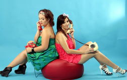 Two young women calling on phones on blue background. Two young women calling on phones sit on rad soft chair on blue background Royalty Free Stock Image