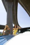 Two young women by car beneath overpass, smiling, portrait, low angle view Royalty Free Stock Images