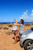 Two young women with car look at map. Two young women with car look at road map on a beach against sea and sky Royalty Free Stock Images