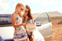 Two young women with car look at road map. With mountain landscape in background Stock Photography