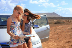 Two young women with car look at road map. With mountain landscape in background Stock Photos