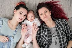 Two young women, a lesbian homosexual couple, are lying on a blanket with a child. Same-sex marriage, adoption. Two young women in casual clothes and with pink royalty free stock images