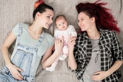 Two young women, a lesbian homosexual couple, are lying on a blanket with a child. Same-sex marriage, adoption. stock photo
