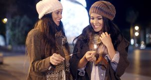 Two young women celebrating Christmas. Outdoors in winter in a town square standing holding sparklers and smiling and laughing in their stylish winter outfits stock video