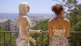 Two young women chatting on a balcony. Two attractive stylish young women chatting on a balcony or outdoor patio leaning on a metal rail overlooking a city stock footage