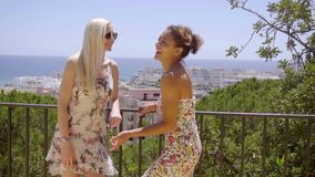 Two young women chatting on a balcony. Two attractive stylish young women chatting on a balcony or outdoor patio leaning on a metal rail overlooking a city stock video footage