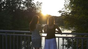 Two young women chatting outdoor at sunset. Two young girlfriends talking in the park near lake at sunset with beautiful glare on their hair, slow motion stock video footage