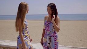 Two young women chatting on a seafront promenade. Two attractive young women in trendy dresses standing chatting on a seafront promenade overlooking the ocean stock footage